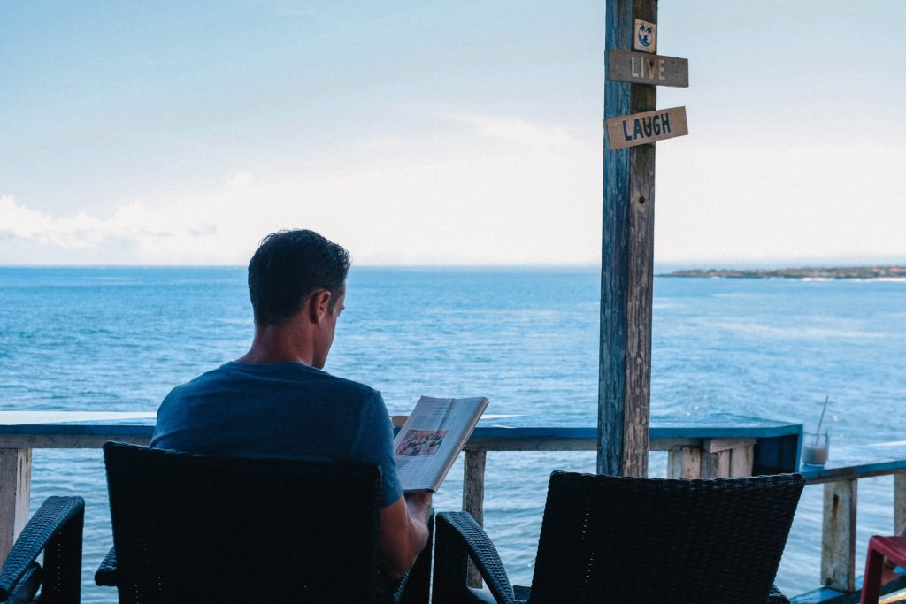 Employee enjoying reading a book at the beach during a well-being day.
