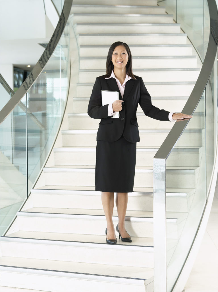 A business woman taking the stairs at work